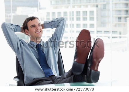 Happy manager relaxing in his office - stock photo