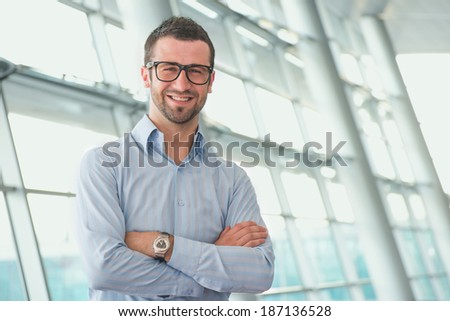 Happy manager standing with his arms crossed in modern glass and steel building - stock photo