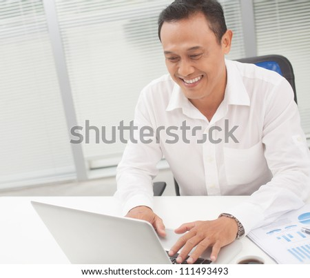 Happy manager typing on laptop at his table