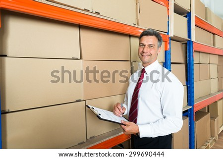 Happy Manager Writing On Clipboard In Distribution Warehouse - stock photo