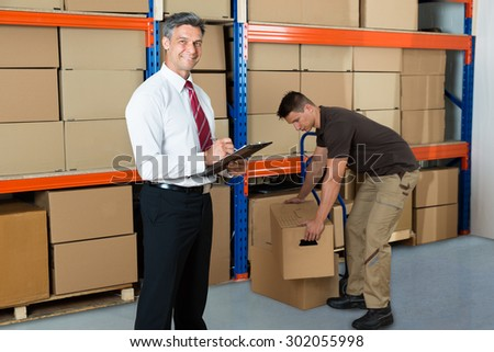 Happy Manager Writing On Clipboard While Worker Carrying Box In Warehouse - stock photo