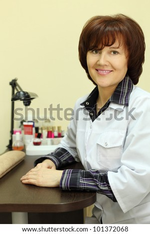 Happy manicurist dressed in white robe sits at table for manicure in beauty salon - stock photo