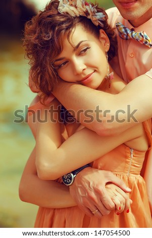 Happy marriage concept. Portrait of a beautiful couple of hipsters in trendy clothing hugging. Peach colored clothing. Wedding day. Close up. Outdoor shot