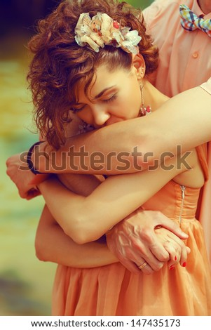 Happy marriage concept. Portrait of a beautiful couple of hipsters in trendy clothing hugging. Bride kissing groom's hand. Peach colored clothing. Wedding day. Close up. Outdoor shot