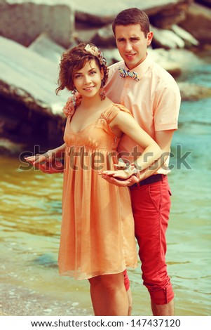 Happy marriage concept. Portrait of a beautiful couple of hipsters in trendy clothing standing at the seaside. Wedding day. Outdoor shot