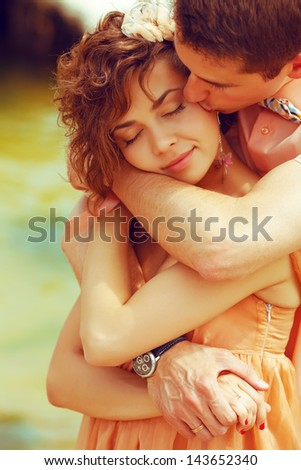 Happy marriage concept. Portrait of a beautiful kissing couple of hipsters in trendy clothing. Wedding day. Close up. Outdoor shot - stock photo