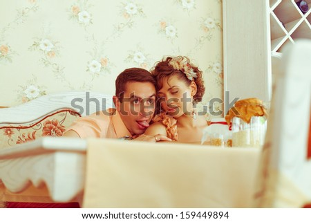 Happy marriage concept. Portrait of a beautiful married couple of hipsters in trendy clothing having fun in vintage cafe. Wedding day. Copy-space. Indoor shot - stock photo