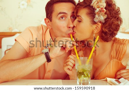 Happy marriage concept. Portrait of a beautiful married couple of hipsters in trendy clothing drinking mojito and kissing in vintage cafe. Wedding day. Close up. Indoor shot - stock photo