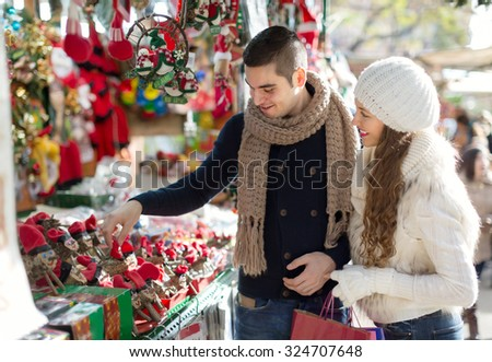 Happy married couple at Catalan Christmas market. smiling - stock photo