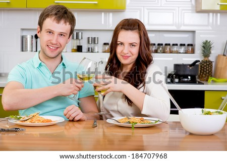Happy married couple clinking glasses with wine at the kitchen at home