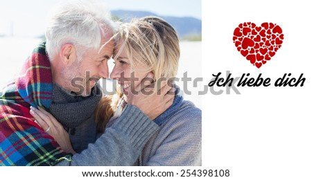 Happy married couple embracing on the beach against ich liebe dich - stock photo