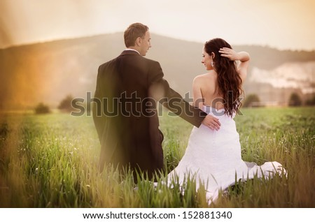 Happy married couple enjoying wedding day in nature - stock photo