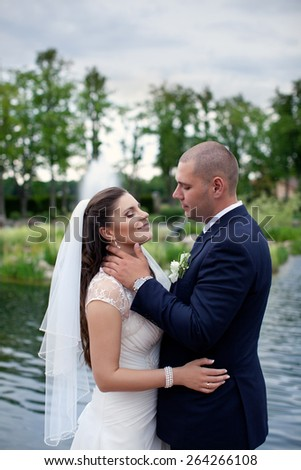 Happy married couple on nature.Beautiful wedding couple.Romantic moment on your wedding day.Newlyweds embracing     - stock photo