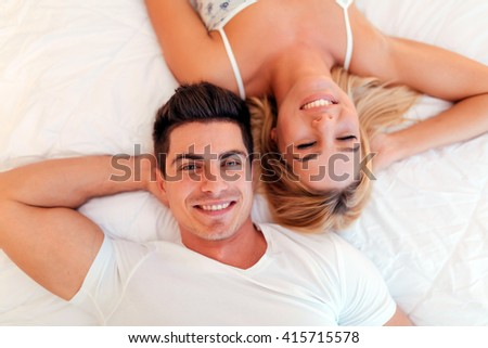 Happy married couple relaxing lying on bed and smiling