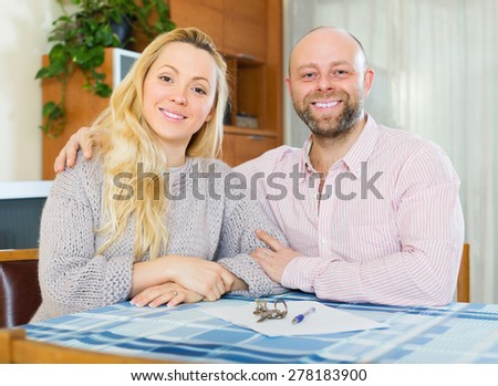 Happy married couple sitting at table with keys and documents  - stock photo