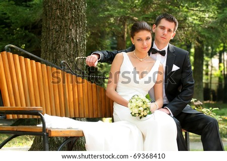 Happy married couple sitting on park bench