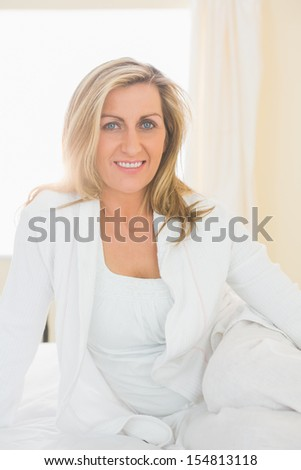 Happy mature blonde woman looking at camera posing on her bed in a bedroom