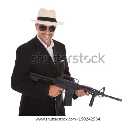 Happy Mature Business Man Holding Gun Over White Background - stock photo