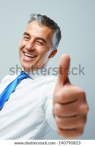 Happy mature business man showing thumbs up sign