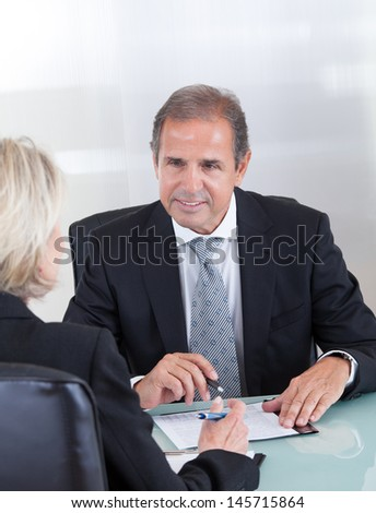 Happy Mature Businessman And Businesswoman In Office