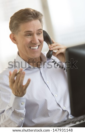 Happy mature businessman communicating on telephone while looking at computer monitor in office - stock photo