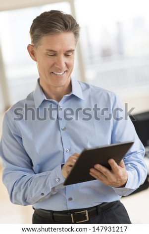 Happy mature businessman looking at digital tablet in office