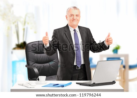 Happy mature businessman standing in his office and giving thumbs up - stock photo
