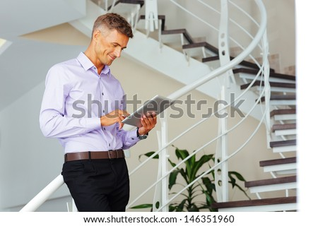Happy mature businessman using his tablet - stock photo