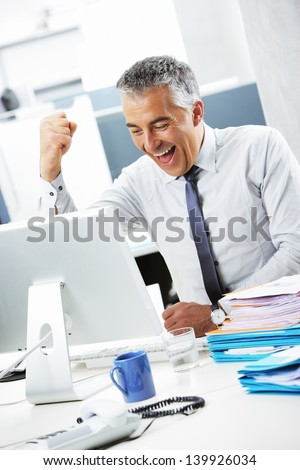 Happy mature businessman while working on computer at desk in office - stock photo
