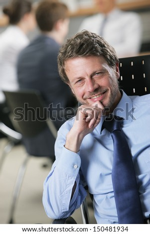 Happy mature businessman with colleagues in the background - stock photo