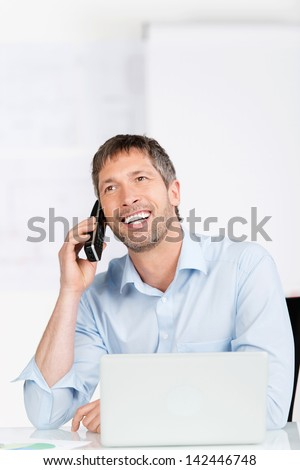 Happy mature businessman with laptop using cordless phone at office desk - stock photo