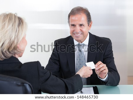 Happy Mature Businesspeople Exchanging Visiting Card In Office