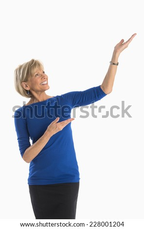 Happy mature businesswoman gesturing towards copy space against white background - stock photo