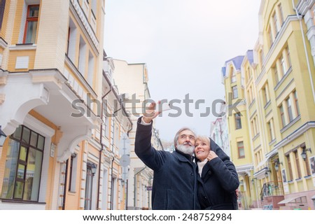 Happy Mature caucasian couple making selfie standing together on street - stock photo