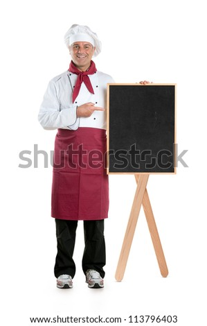 Happy mature chef showing dish of the day on a black board isolated on white background
