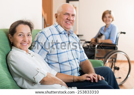 Happy mature couple and  daughter in wheelchair  - stock photo