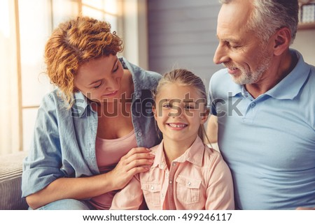 Happy mature couple and their little granddaughter are hugging, talking and smiling while sitting on sofa at home