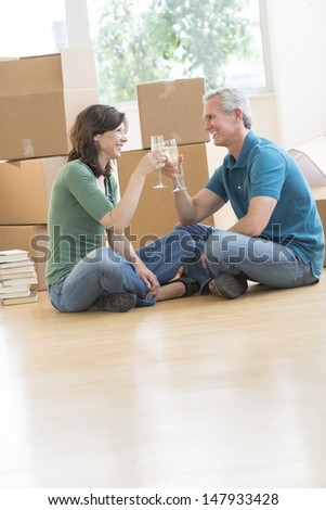 Happy mature couple celebrating with champagne against cardboard boxes in new house - stock photo