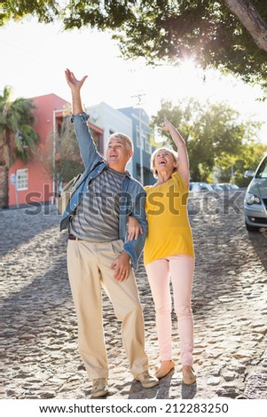 Happy mature couple cheering in the city on a sunny day
