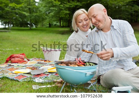 Happy mature couple cooking meat on portable barbecue at an outdoor picnic in forest park