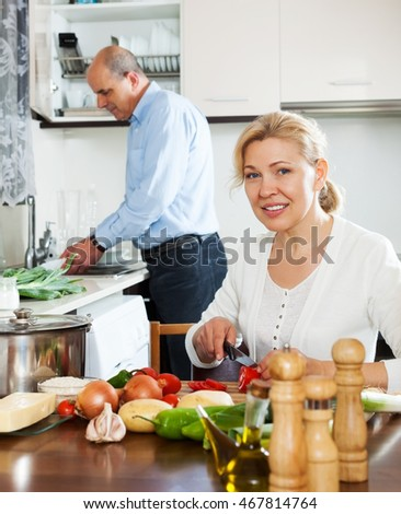 happy mature couple cooking soup at home kitchen