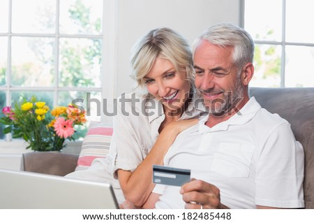 Happy mature couple doing online shopping through laptop and credit card at home - stock photo