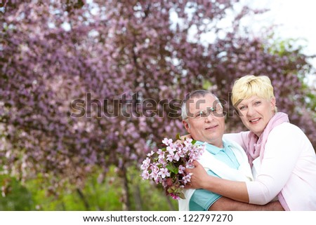 Happy mature couple embracing in blooming garden