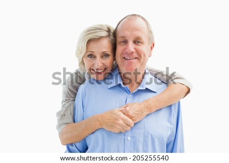 Happy mature couple embracing smiling at camera on white background - stock photo