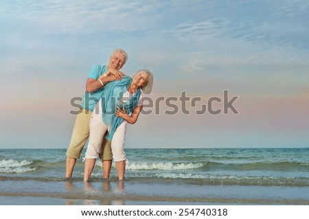 Happy Mature couple enjoy fresh air on beach - stock photo