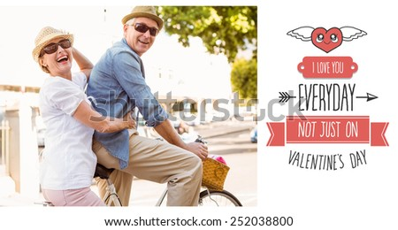 Happy mature couple going for a bike ride in the city against cute valentines message - stock photo
