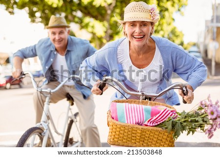 Happy mature couple going for a bike ride in the city on a sunny day - stock photo