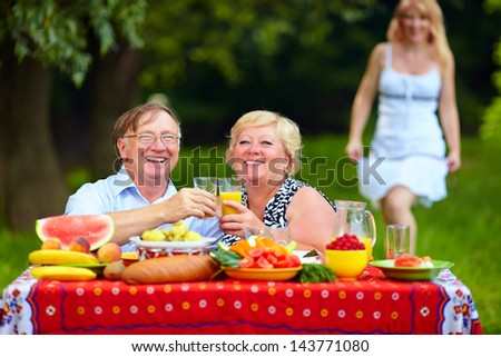 happy mature couple having picnic outdoors - stock photo