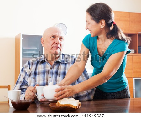 Happy mature couple having tea at home interior