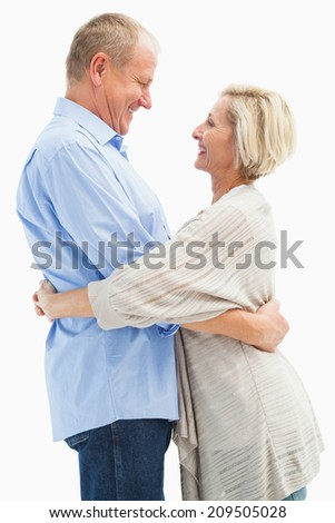 Happy mature couple hugging and smiling on white background